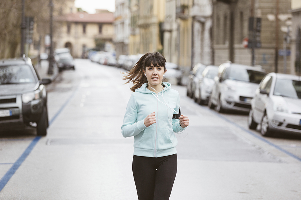 Beautiful Young Woman Jogging Alone on City Street
